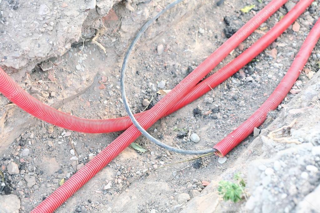 Прокладка стальной трубы для кабеля в земле.